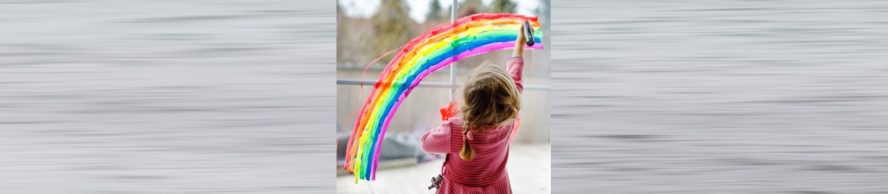 young girl painting a bright rainbow in a window